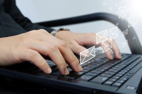 fingers on a laptop with email icons suggesting someone sending emails