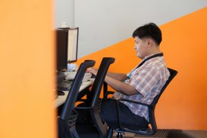 A Male Outsourcing Employee in Checkered doing Content Writing Tasks in front