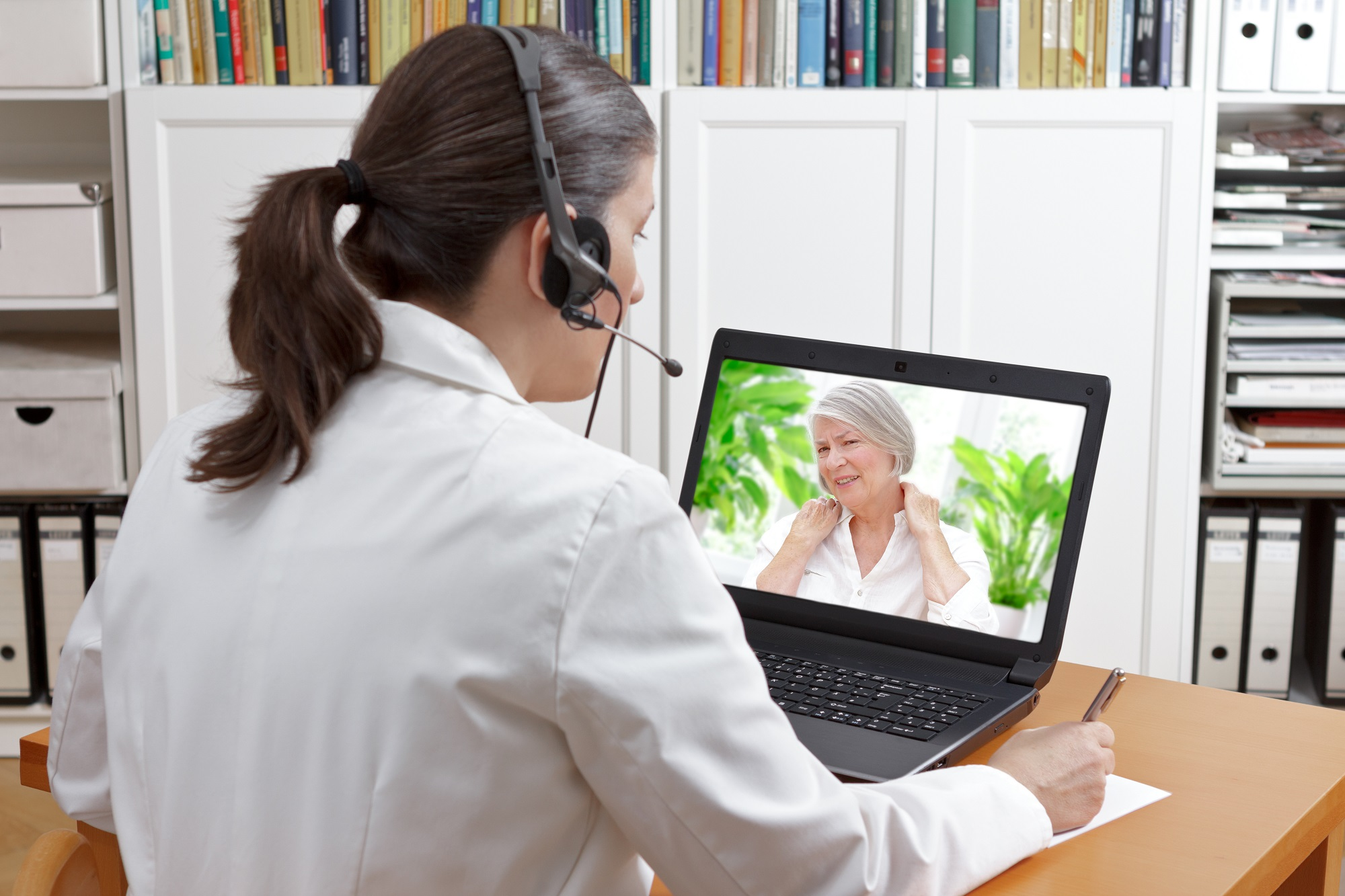 a female telemedicine practitioner attending to an elderly lady over a laptop