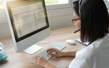 female outsourcing employee with headset working on computer