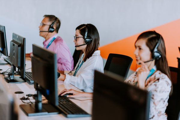 3 outsource employees with headsets working on their computers