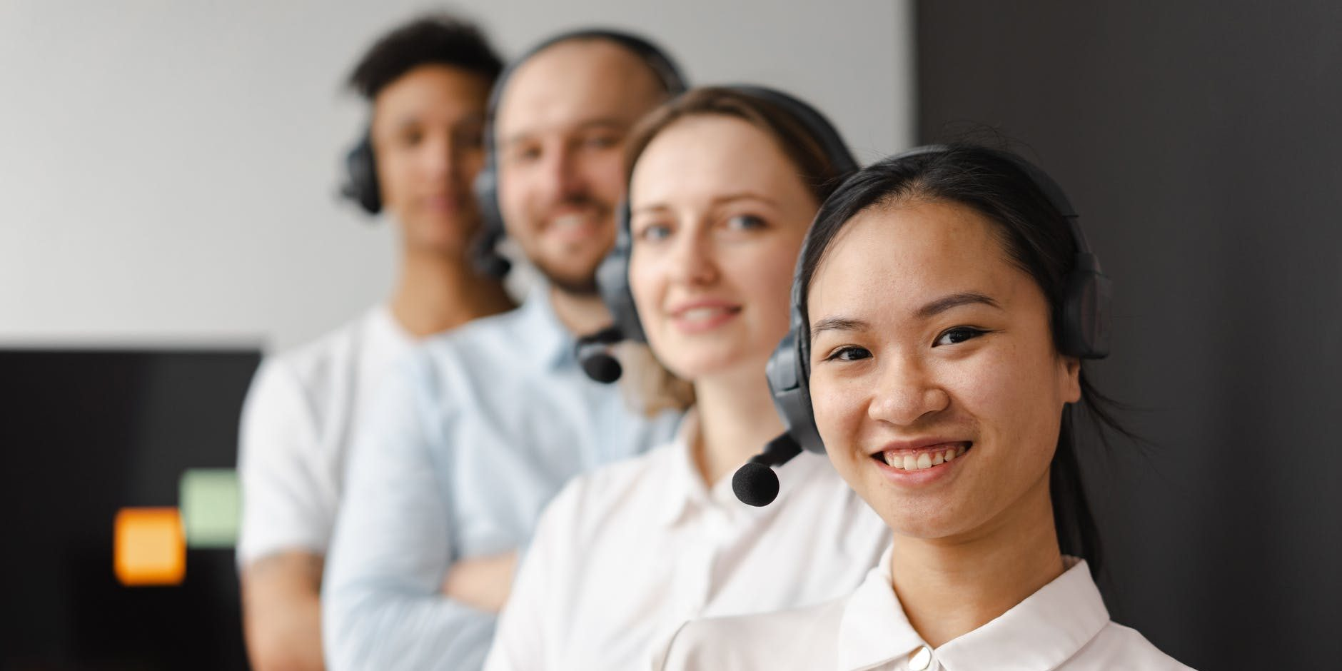 outsource staff with headsets smiling - passionately working in a call center